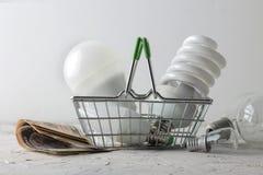 El concepto de electricidad del ahorro dinero y diversos bulbos en una cesta en un fondo ligero la opción entre económico imagen de archivo libre de regalías