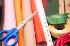 El concepto de Griftwrapping, las tijeras del primer, los papeles y las cintas se separaron hacia fuera en superficie de madera Imágenes de archivo libres de regalías