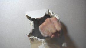El concepto de la agresión, pared está quebrado a través por un puño almacen de video