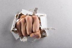El concepto de la agresión, pared está quebrado a través por un puño Imagen de archivo libre de regalías