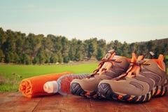 El concepto de la aptitud con calzado del deporte, la toalla y la botella de agua sobre la tabla de madera delante del campo ajar Foto de archivo libre de regalías
