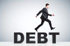 El concepto de la deuda con el funcionamiento del hombre de negocios corre en palabra de la deuda fotos de archivo libres de regalías