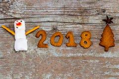 El concepto 2018 de la Feliz Año Nuevo - muñeco de nieve divertido de la melcocha y entumece Imagen de archivo