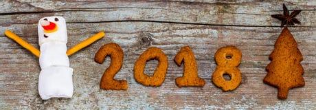 El concepto 2018 de la Feliz Año Nuevo - muñeco de nieve divertido de la melcocha y entumece Fotografía de archivo