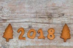 El concepto 2018 de la Feliz Año Nuevo - numere 2018 con el pan de jengibre en el wo Imágenes de archivo libres de regalías
