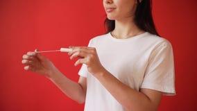 El concepto de la menstruación, ovulación en muchachas Muchacha en un fondo rojo que sostiene un tapón, junta metrajes