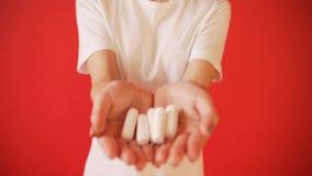 El concepto de la menstruación, ovulación en muchachas Muchacha en un fondo rojo que sostiene un tapón, junta almacen de video