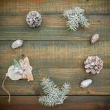 El concepto de la Navidad o del Año Nuevo con los conos, el pan de jengibre y el abeto del pino ramifica en fondo de madera Endec Imágenes de archivo libres de regalías