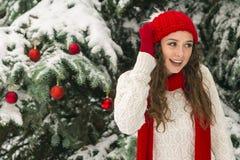 El concepto de la Navidad y del Año Nuevo Ambientes del invierno La muchacha en el rojo y sombrero de los guantes cerca del árbol fotografía de archivo
