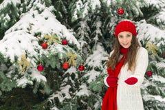 El concepto de la Navidad y del Año Nuevo Ambientes del invierno La muchacha en el rojo y sombrero de los guantes cerca del árbol imagenes de archivo