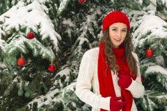 El concepto de la Navidad y del Año Nuevo Ambientes del invierno La muchacha en el rojo y sombrero de los guantes cerca del árbol fotografía de archivo libre de regalías
