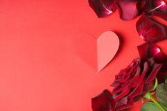 El concepto de la pasión con rojo oscuro subió, pétalos y un corazón de papel Fotos de archivo libres de regalías