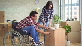 El concepto de mudanza, un hombre discapacitado en una silla de ruedas recoge una mesita de noche al lado de su esposa almacen de video