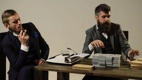 El concepto de negocio sombrío Dos hombres en trajes cuentan los cigarros del dinero y del humo que se sientan en la tabla almacen de video