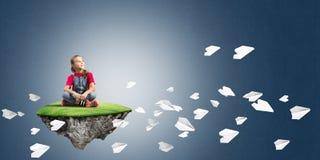 El concepto de niñez feliz descuidada con la muchacha y el papel acepilla el vuelo alrededor Imágenes de archivo libres de regalías