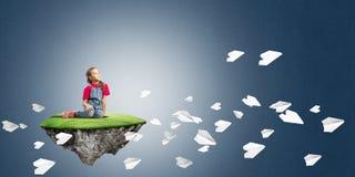 El concepto de niñez feliz descuidada con la muchacha y el papel acepilla el vuelo alrededor Imagen de archivo libre de regalías