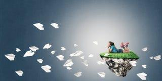 El concepto de niñez feliz descuidada con la muchacha y el papel acepilla f Fotografía de archivo