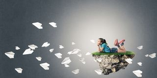 El concepto de niñez feliz descuidada con la muchacha y el papel acepilla f Foto de archivo