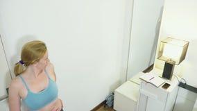 El concepto de pérdida del exceso de peso y de peso Una mujer se mide con una cinta métrica en el dormitorio mirada almacen de metraje de vídeo