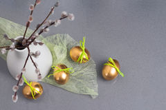 El concepto de Pascua, los huevos de oro y el sauce de gatito ramifica, el florero blanco en el top de la cocina del cuarzo Imágenes de archivo libres de regalías