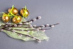 El concepto de Pascua, los huevos de oro y las ramas del sauce de gatito en cocina del cuarzo rematan Imágenes de archivo libres de regalías