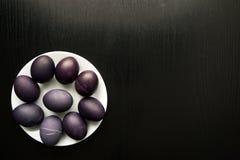 El concepto de Pascua pintó los huevos en fondo negro en la placa blanca f Foto de archivo