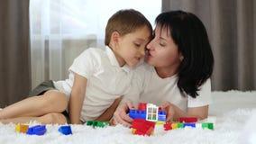 El concepto de relación del madre-niño El bebé y la mamá felices están jugando meccano mientras que miente en el sofá Una madre almacen de video