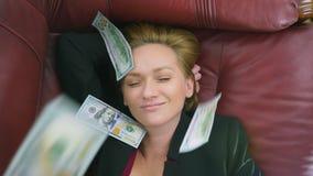 El concepto de renta pasiva la mujer feliz miente en el sofá y las sonrisas, encima de ella los dólares que caen 4k, primer almacen de video
