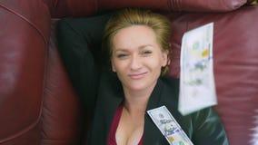 El concepto de renta pasiva la mujer feliz miente en el sofá y las sonrisas, encima de ella los dólares que caen 4k, primer almacen de metraje de vídeo