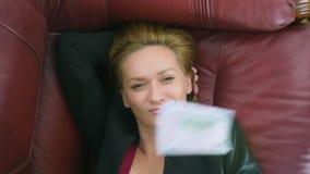 El concepto de renta pasiva la mujer feliz miente en el sofá y las sonrisas, encima de ella los dólares que caen 4k, primer metrajes