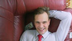 El concepto de renta pasiva una persona feliz está mintiendo en el sofá y sonriendo, los dólares encima de él están cayendo 4K metrajes