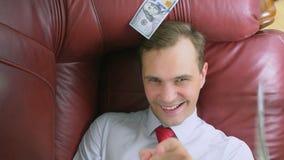 El concepto de renta pasiva una persona feliz está mintiendo en el sofá y sonriendo, los dólares encima de él están cayendo 4K almacen de video