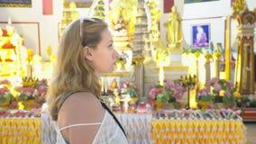 El concepto de turismo en Asia Turista europeo de la mujer con el pelo blanco y los ojos azules que ve las vistas en un budista almacen de video