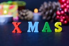 El concepto de un Año Nuevo, Navidad La palabra de letras multicoloras en fondo de madera de la Navidad con los regalos, conos de Foto de archivo libre de regalías