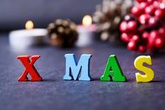 El concepto de un Año Nuevo, Navidad La palabra de letras multicoloras en fondo de madera de la Navidad con los regalos, conos de Imágenes de archivo libres de regalías