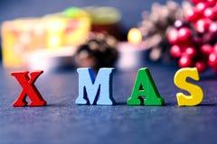 El concepto de un Año Nuevo, Navidad La palabra de letras multicoloras en fondo de madera de la Navidad con los regalos, conos de Fotos de archivo libres de regalías