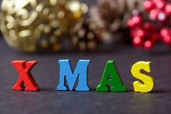 El concepto de un Año Nuevo, Navidad La palabra de letras multicoloras en fondo de madera de la Navidad con los regalos, conos de Foto de archivo
