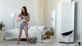 El concepto de una familia joven moderna en un apartamento blanco La mamá pone al bebé para acostar el canto le de una nana almacen de metraje de vídeo
