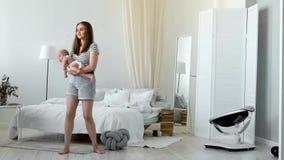 El concepto de una familia joven moderna en un apartamento blanco La mamá pone al bebé para acostar el canto le de una nana metrajes