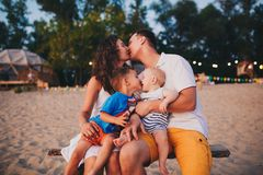 El concepto de vacaciones de familia Familia joven y dos hijos que se sientan en un banco por la tarde en una playa arenosa Beso  foto de archivo libre de regalías