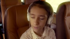 El concepto de vacaciones de verano, viaje Paseos adolescentes de la muchacha en un minivan con los auriculares metrajes