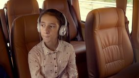 El concepto de vacaciones de verano, viaje Paseos adolescentes de la muchacha en un minivan con los auriculares almacen de metraje de vídeo