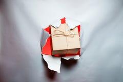 El concepto del Año Nuevo de la Navidad, regalo se rompe a través del papel, con el plac Fotos de archivo