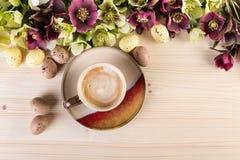 El concepto del café con la primavera florece los huevos de Pascua en la madera ligera Fotos de archivo libres de regalías