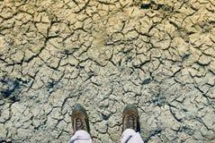 El concepto del cambio de clima, hombre en zapatos sucios se coloca en la grieta secada Foto de archivo libre de regalías