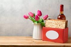 El concepto del día de fiesta de la pascua judía con la botella de vino, el matzoh y el tulipán florece Fotografía de archivo libre de regalías