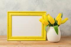 El concepto del día de fiesta de Pascua con el marco y el tulipán en blanco de la foto florece en la tabla de madera Imagen de archivo