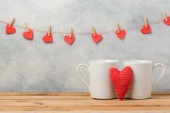 El concepto del día de tarjetas del día de San Valentín con las tazas del café con leche y el corazón forman Imagenes de archivo