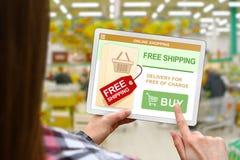 El concepto del envío gratis, muchacha sostiene la tableta digital en fondo borroso de la tienda Fotografía de archivo libre de regalías