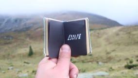 El concepto del escape o del viaje, un viajero en las montañas sostiene un libro con una inscripción metrajes